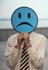 man holding sad emoticon