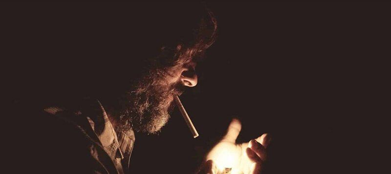 man lighting a cigarette in the dark
