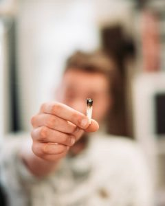 a blurred person holding a cannabis cigarette