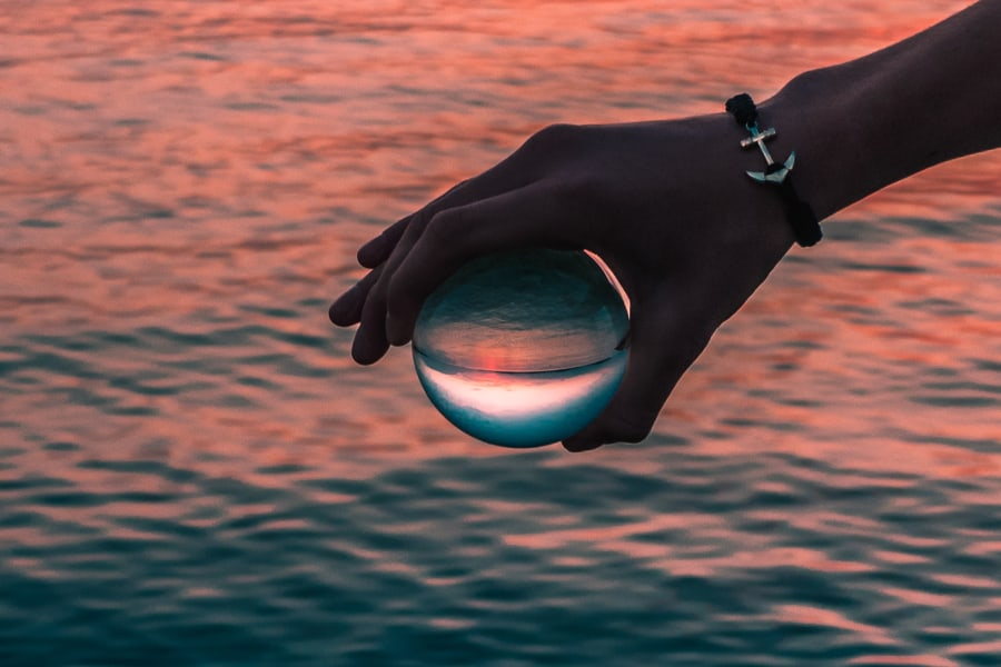 hand holding a glass ball over water