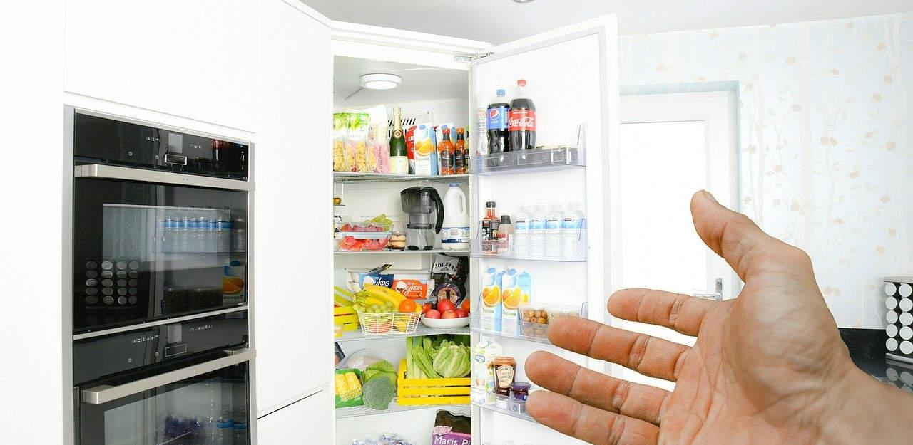 hand gesturing towards an open fridge