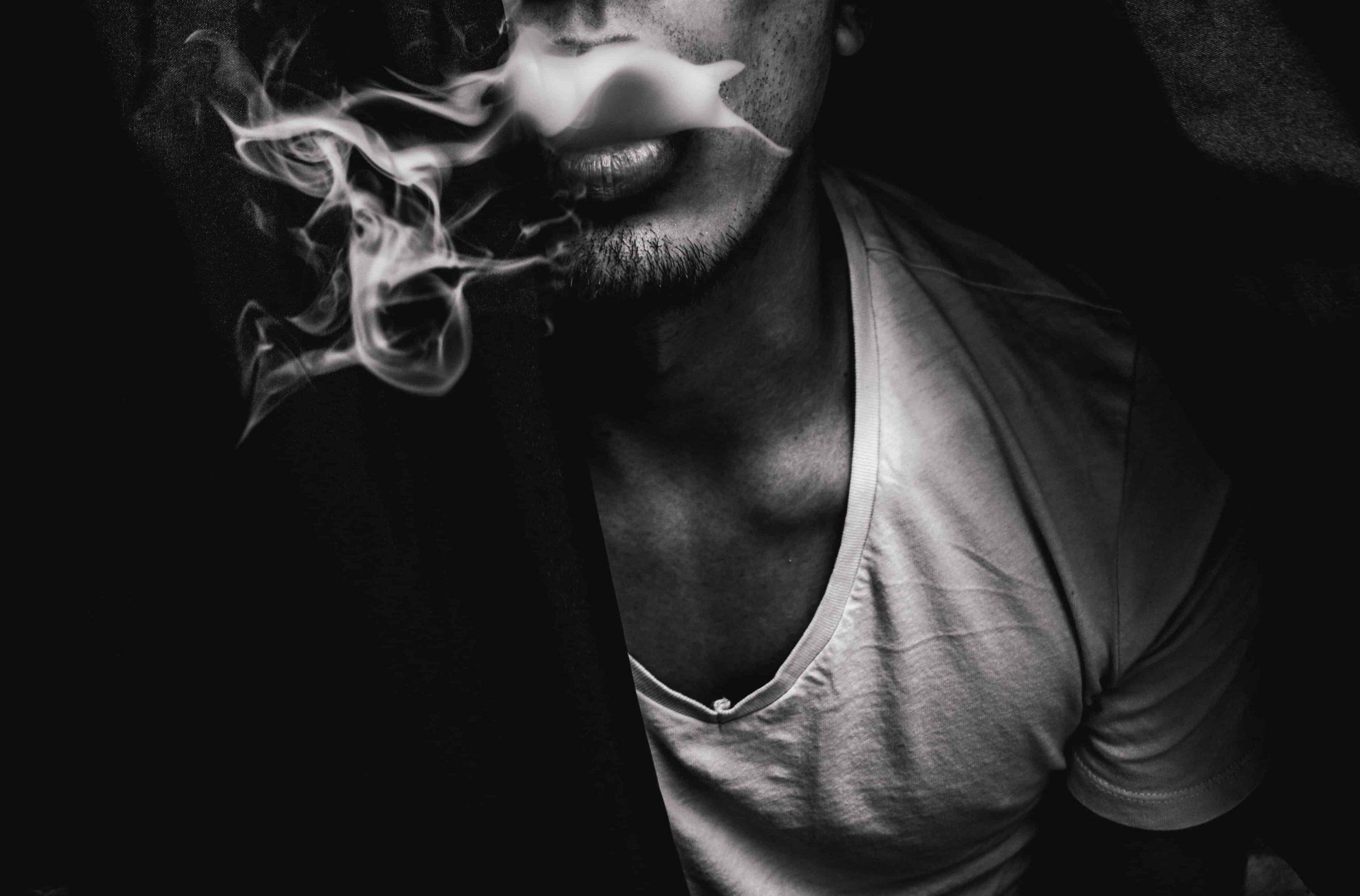 man exhaling smoke from his thc vape pen
