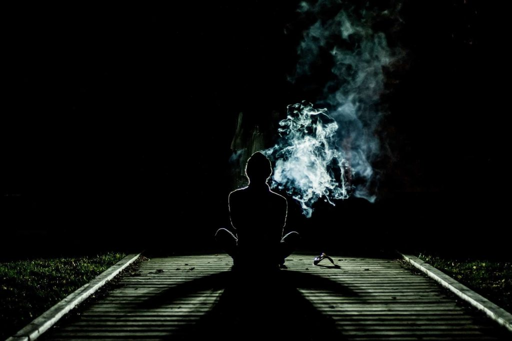 a person exhaling smoke on black background
